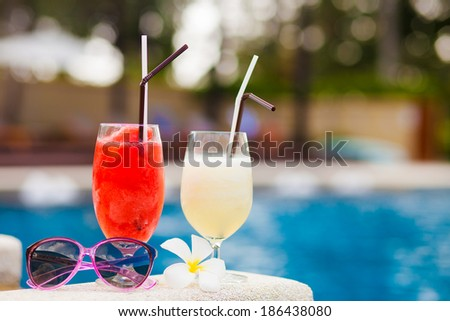 two glasses of cocktails and sunglasses near pool - stock photo