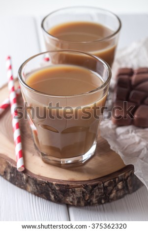 Two glasses of coffee and straws on white background