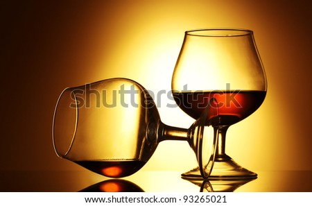 Two glasses of cognac on yellow background - stock photo