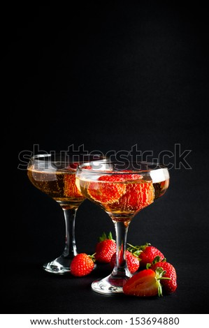 Two glasses of cold champagne with strawberries on a black background, close-up - stock photo
