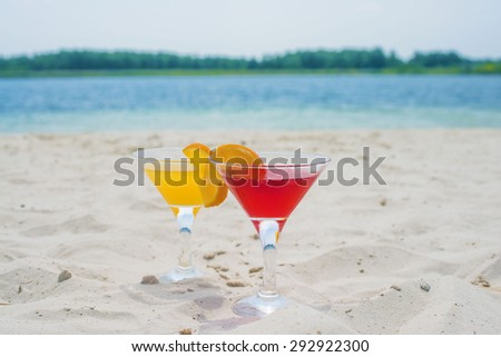 two glasses of cold red drink with a slice of orange on a summer day, Coctails in transparent goblet against white sand texture , blue water and summer sky background  - stock photo