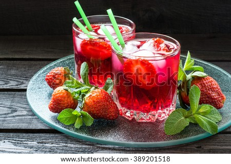 Two glasses of cold refreshing drink with strawberries, ice and cocktail straws on a glass tray with fresh strawberries and mint. Selective focus - stock photo