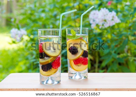 Two glasses of delicious refreshing drink. Infused water with berries,  golden kiwi and mint.