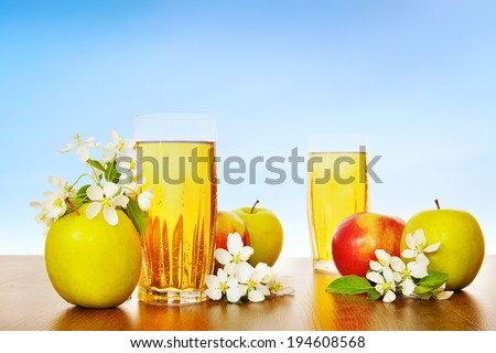 Two glasses of fresh apple juice with ripe apples against blue sky - stock photo