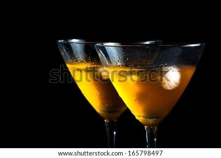 two glasses of fresh cocktail with ice on black background with space for text