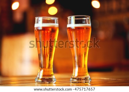 Two glasses of fresh cold light beer on a wooden bar counter in pub with free space for your text. Beautiful background of the Oktoberfest. fine grain. Soft focus. Shallow DOF