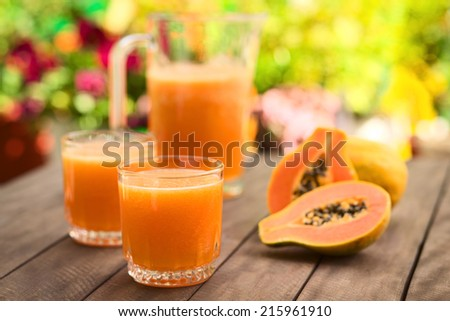 Two glasses of freshly prepared papaya juice with pitcher and papaya fruits in the back on table outdoors (Selective Focus, Focus on the front rim of the first glass)  - stock photo