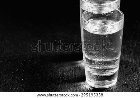 Two glasses of gin on a dark background, black and white, selective focus