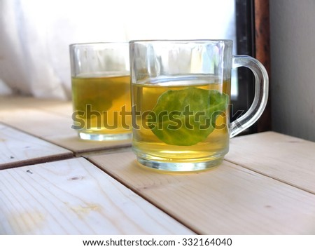 Two glasses of green tea with natural light from window.