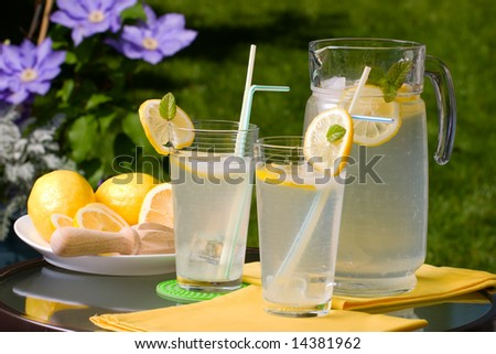 Two glasses of home made iced cold lemonade and pitcher on hot summer. - stock photo