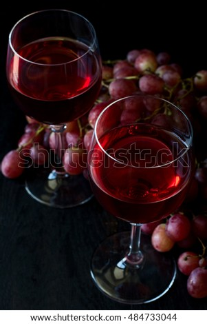 Two glasses of homemade rose wine and grapes on black wooden table. Low key
