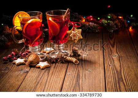 Two glasses of hot mulled wine with oranges and spices - stock photo