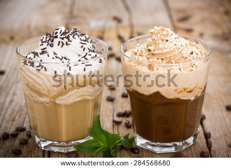 Two glasses of ice coffee with milk and whipped cream - stock photo