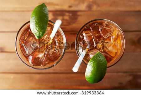two glasses of iced sweet tea with lime and retro paper straws shot overhead on wooden table - stock photo