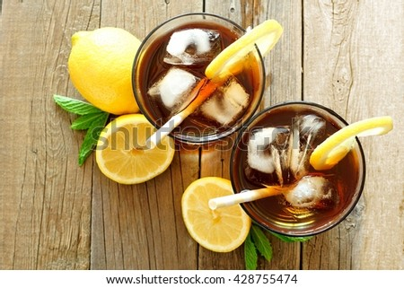 Two glasses of iced tea with lemon, overhead view on a rustic wooden background