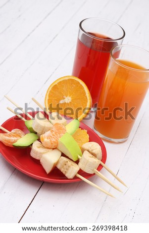 Two glasses of juice, orange and fruit on the table. Fruit skewers. Appetizer, dessert. Kitchen white table. Avocado, Apple, orange, tangerine, banana. Tasty and healthy. - stock photo