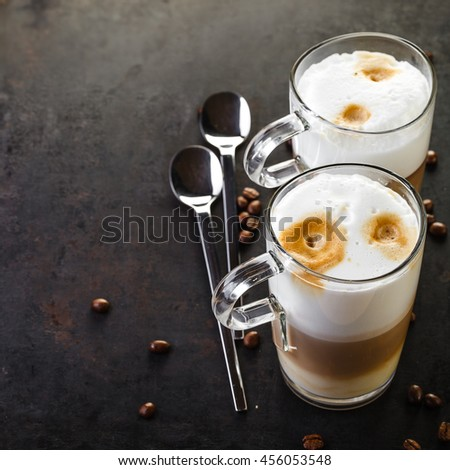two glasses of latte ad spoons on dark rustic background