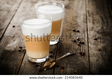 Two glasses of latte coffee beans and spoon on old wooden table. - stock photo