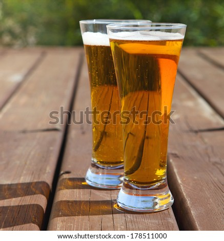 Two glasses of light beer on a table outdoors. Summertime - stock photo