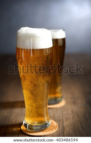 Two glasses of light beer on wooden table - stock photo