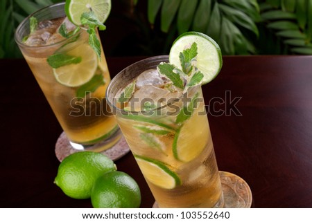 Two glasses of lime and mint iced tea garnished with lime and mint on a table in a restaurant on a tropical beach. - stock photo