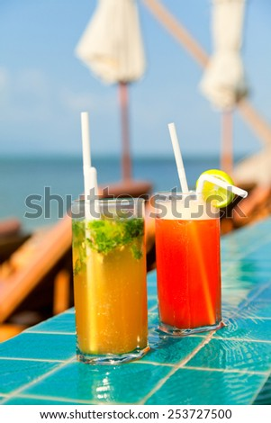 Two glasses of Mai Thai and Mojito Cocktails at the pool in a family hotel in Ko Samui, Thailand - stock photo