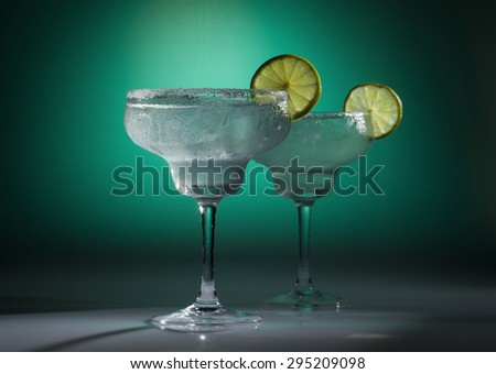 Two glasses of margarita cocktail on a green background. - stock photo