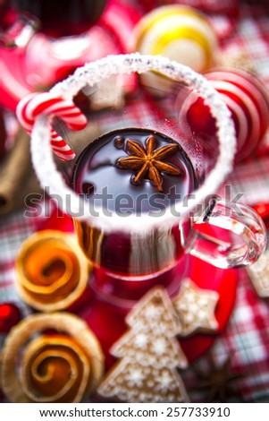 Two glasses of Mulled wine decorated with sugar rim and candy along with spices, fruit, gingerbread cookies and Christmas decorations on checkered red and green cloth. - stock photo