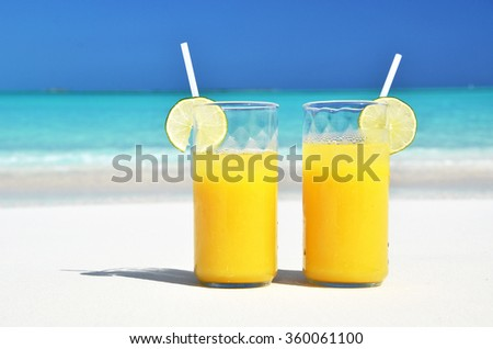 Two glasses of orange juice on the sandy beach - stock photo