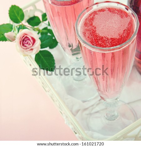 Two glasses of pink champagne with a rose on a vintage pastel color background - stock photo