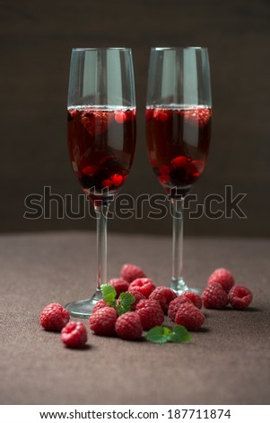 two glasses of prosecco with wild berries - stock photo