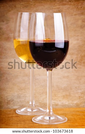 two glasses of red and white wine on a wooden background - stock photo