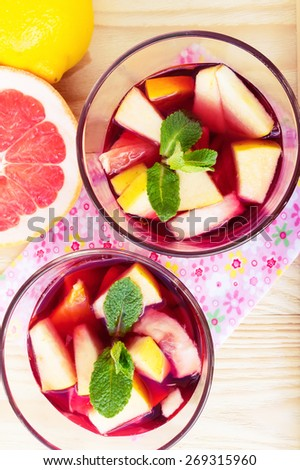 Two glasses of red sangria with limes oranges, apples and grapefruits, top view - stock photo