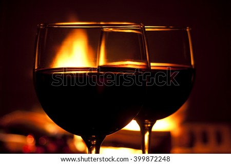 Two glasses of red wine against a roaring fire - stock photo