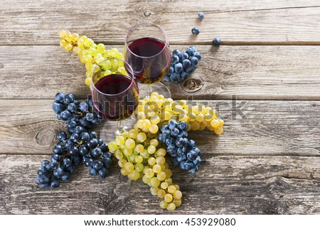 two glasses of red wine and grapes on rusty wooden table - stock photo