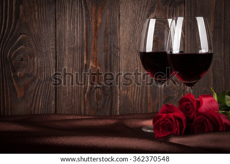 Two glasses of red wine and red roses on brown silk - stock photo