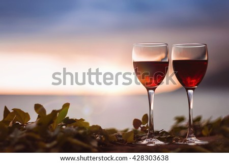Two glasses of red wine at sunset, on a seascape background - stock photo