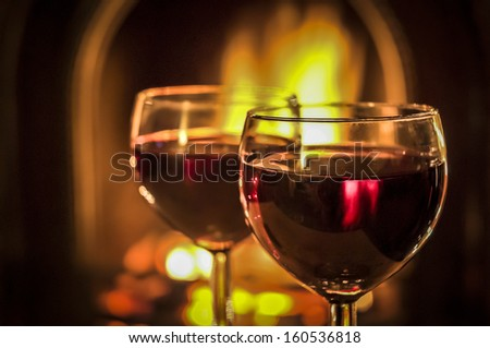 Two glasses of red wine beside the fire. - stock photo