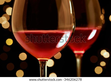 Two glasses of red wine close up with candle lights in the background.