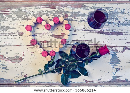 Two glasses of red wine, heart with corks and rose in a vintage style. - stock photo