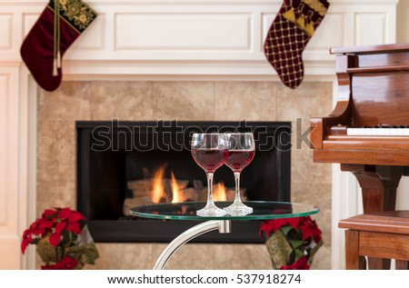 Two glasses of red wine on top of glass table with glowing fireplace, piano and holiday decorations in background