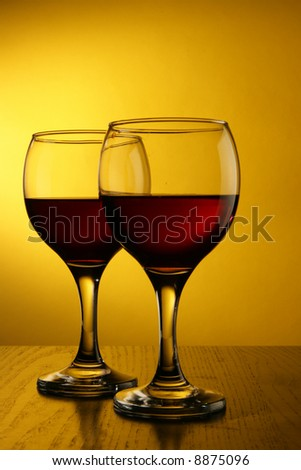 Two glasses of red wine over yellow background