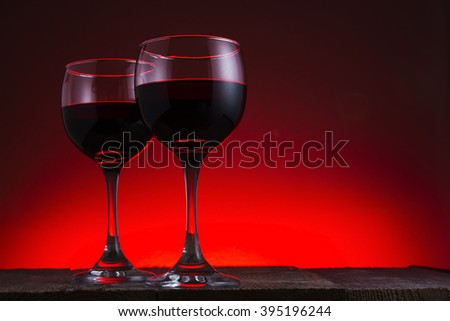Two glasses of red wine with a da background on a wooden table