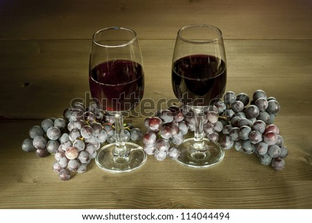 two glasses of red wine with clusters of grapes on wooden table