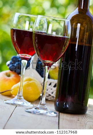 Two glasses of red wine with wine bottle on the table