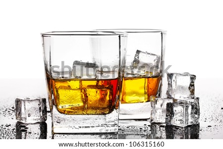 two glasses of scotch whiskey and ice on table isolated on white - stock photo
