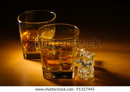 two glasses of scotch whiskey and ice on wooden table