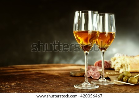 Two glasses of sherry served with tasty traditional Spanish tapas of olives, salami and fresh bread on an old wooden table with copy space