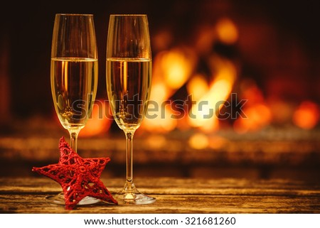 Two glasses of sparkling champagne in front of warm fireplace. Cozy relaxed magical atmosphere in a chalet. Holiday concept. Beautiful background with shimmering wine, decorated with red star. - stock photo