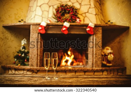 Two glasses of sparkling champagne in front of warm fireplace. Cozy relaxed magical atmosphere in a chalet house by the fireside. Snug holiday concept. Beautiful background with shimmering wine. - stock photo